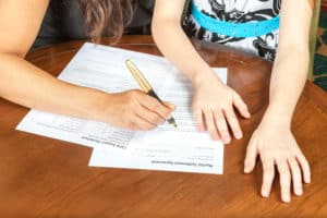 Woman with daughter signing a document.